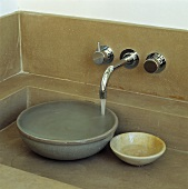 Wasser fliesst aus einem Edelstahl-Wasserhahn in eine Keramikschale