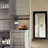 Einbauschränke und Spritzschutz aus Edelstahl in einer modernen Küche, im Hintergrund ein grosser Spiegel in der Diele