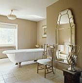 Ein antiker vergoldeter Stuhl vor einem großen Wandspiegel in einem hellen Badezimmer mit frei stehender Badewanne