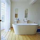 Eine frei stehende weisse Badewanne in einem Badezimmer mit Kieferboden
