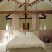 Bett mit weißen Kissen und Decke in einem Mezzanine-Schlafzimmer mit Balken und rosa Wänden