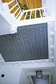 Blick von unten auf eine grau und weiss gemusterte Decke und auf ein Treppengeländer
