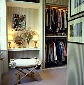 Männliches Ankleidezimmer mit gestreifter Tapete, offenem Kleiderschrank, Regal mit brennenden Tischlampen und einem Hocker
