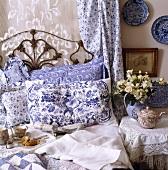 Nahaufnahme von einem schmiedeeisernen Bett mit blau-weiss gemusterten Kissen, Spitzen- und Baumwollvorhang hinter dem Bett und Teekanne auf dem Nachttisch