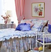 Schlafzimmer mit abstrakt gemusteter Bettdecke in Rosa und Blau, dazu passende Kissen in Rosa und Blau und einem pinkfarbenem Vorhang