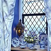 Nahaufnahme von blau-weißem Porzellan auf einer Fensterbank
