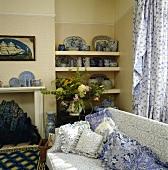 Traditionelles Wohnzimmer mit blau-weiss gemustertem Sofa und dazu passenden Kissen