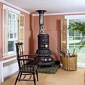 Wohnzimmer mit schwarzem Eisenofen, antikem Lehnstuhl und terracottafarbenen Wänden