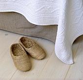 Pantoffeln aus Seegras neben einem Bett