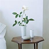 weiße Rose in einer Keramikvase auf einem achteckigen Beistelltisch aus Holz