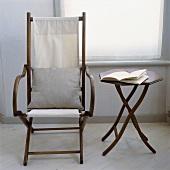 Antique Campaign-Stuhl mit weißem Kissen neben einem kleinen achteckigen Tisch