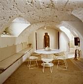 weiße Saarinen-Tisch, Eames-Stühle und Sitzbänke in einem Esszimmer im Keller mit rauer Steindecke