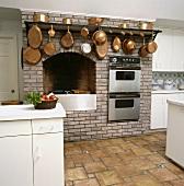 Backsteinmauer mit Einbaugeräten und Kupferpfannen in einer Küche