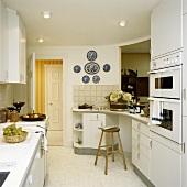 weiße Küche mit Einbaugeräten und einer Frühstücksbar