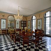 Kronleuchter über antikem Tisch und Stühlen, gewölbte Spiegel und Fenster in einem Esszimmer mit Schachbrettmuster-Boden