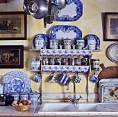 Gewürzregal und blau-weisses Geschirr über dem Spülbecken in einer Küche