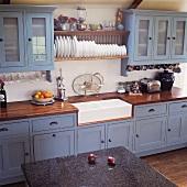 Landhausküche mit blaugrauen Fronten und Küchenboard mit Tellern über weisser Keramikspüle