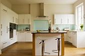 Offene Designerküche in Weiss mit Barhockern aus Chrom und Acrylglas vor freistehender Küchentheke