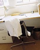 Arbeitsecke mit Tischplatte aus Holz über Container und Hose über Schreibtischstuhl aus schwarzem Leder und Chrom
