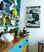 Keramik mit Gemüsemotiven am Regal hängend über Küchenschrank mit türkisfarbenen Schubladen im südländischem Flair