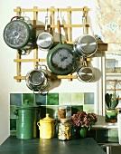 Pfannen und Töpfe am Wandboard hängend über grünen Wandfliesen und Keramikgefässen auf Ablage