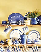 Weiss blaues Keramikservice auf Küchenregal vor gelb getönter Wand