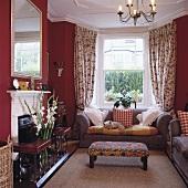 Traditionelles Wohnzimmer mit rot getönten Wänden und gepolstertem Hocker vor moderner Sofagarnitur im Erker