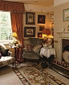 Ein viktorianischer Sessel und kleiner runder Tisch im Wohnzimmer neben dem Kamin