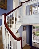 Weisses Treppengeländer mit Mahagoni-Handlauf in einer blauen Halle