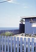 Blaues Holzhäuschen mit blauem Zaun am Meer an der Ostküste der USA