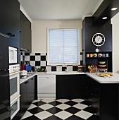 Schwarz-weisse Wand- und Bodenfliesen in Schachbrettmuster, schwarze Küchenschränke und weisse Küchengeräte