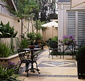 Möbel aus Metall auf gefliester und gepflasterter Terrasse in einem modernen Stadtgarten im Sommer