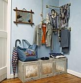 Kleidung auf Garderobe aus Messing auf pastellblauer Wand und alte bemalte Truhe