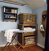 Altes Bügelbrett aus Holz vor rustikalem Holzregal und Korb vor pastellblauer Wand