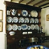 Antiker Geschirrschrank aus dunklem Holz mit blau weißem Porzellan im Landhaus-Esszimmer