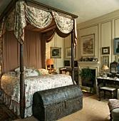 Himmelbett mit drapiertem Baldachin und dunklem Holzgestell mit antiker Truhe am Bettende