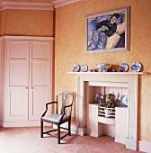 Altbauwohnraum mit apricotfarbenen Wänden mit weißem Kamin neben Stuhl und Einbauschrank