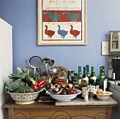 Gemüse in Schalen und Weinflaschen auf Küchenunterschrank