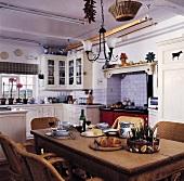 Brotzeit auf Holztisch in weisser Landhausküche