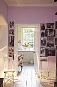 weiße Klappstühle vor rosa Wand mit Fotografien und offener Tür mit Blick ins Bad
