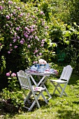 Teepause im Garten mit weißem Tisch und Stühlen