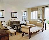 Antike Chaiselongue und helle Sofagarnitur im Wohnzimmer mit antiker Kaminverkleidung