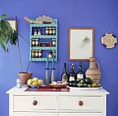 weiße Holzkommode mit Weinflaschen und Schalen mit Obst vor blauer Wand