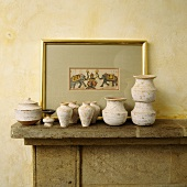 Rustikale Töpfe und Amphoren aus Keramik vor Bild auf Kaminsims