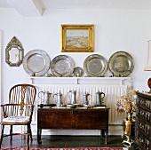 Antiker Holzstuhl neben Kommode mit Zinnkrügen vor Sammlung mit Zinntellern auf Heizkörper