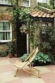 Liegestuhl auf Terrasse vor Haus mit Natursteinfassade
