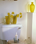 Gelbe Tulpen in gelben Glaskrügen auf Spülkasten und brennende Kerze auf Toilettensitzgarnitur