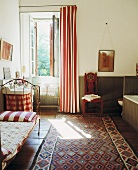 Traditionelles Gästezimmer mit gemustertem Teppich vor Bett und Waschtisch am Fenster