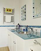 Modernes Badezimmer mit blauer Glasplatte auf Waschtisch und Wandspiegeln