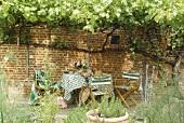 Gartentisch mit Stühlen vor Ziegelwand